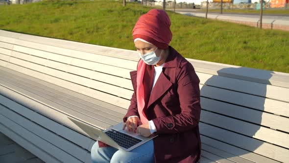 Thumbnail for Young Muslim Woman in a Medical Mask with Laptop Sitting on a Park Bench