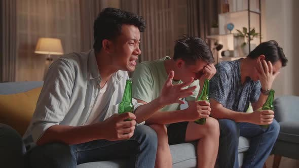 Three Asian Males Cheering And Watching Football Game On Tv And Disappointed At Home