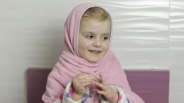 Little Girl with Wet Hair Is Hiding in Pink Towel. Smiles After Bathing