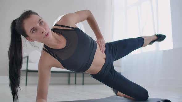 Thumbnail for The Brunette in the Apartment Does an Exercise Lateral Plank Standing on Her Knee and Raising Her