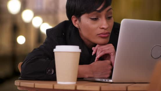 Thumbnail for Pretty African-American female reading something on computer at cafe at night