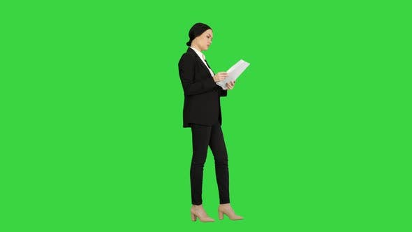 Thumbnail for Serious Brunette Businesswoman Reading Documents on a Green Screen, Chroma Key.