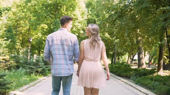 Thumbnail for Beautiful young couple slowly strolling through sunlit bright green park, date