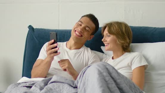 Thumbnail for Young Couple Lying in Bed in the Morning, Using Smartphone
