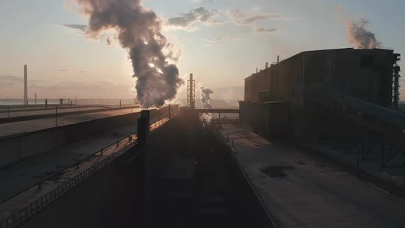 Aerial View. Industrial Zone with Pipe Thick White Smoke Is Poured From the Factory Pipe in Contrast