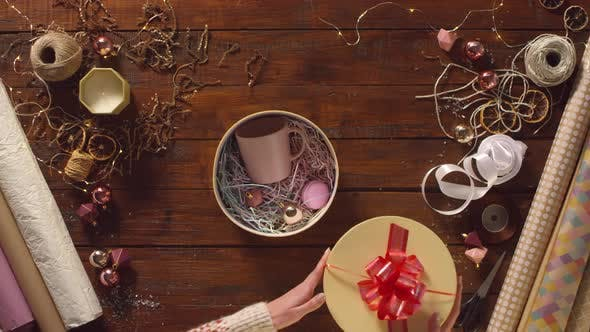 Thumbnail for Woman Unpacking Gift Box with Mug, Macaron and Christmas Bauble