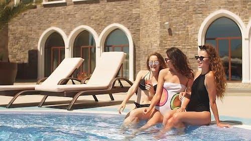 Young Suntanned Models Wearing Swimsuits Sunbathing Near Hotel Pool.