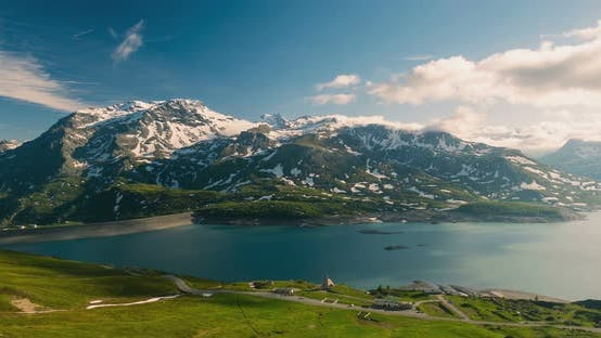Time lapse: mountain peaks and emerald green alpine lake with moving clouds on the italian Alps