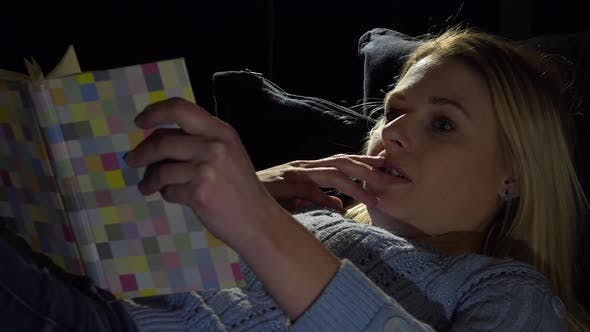 Thumbnail for A Young Beautiful Woman Lies on a Couch in a Dark Room and Reads a Book, Immersed - Closeup