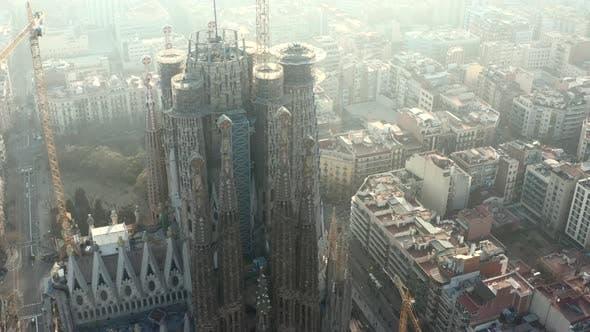Thumbnail for AERIAL: Close Up Circling La Sagrada Familia with Cranes in Beautiful City Sunny Haze Over Barcelona