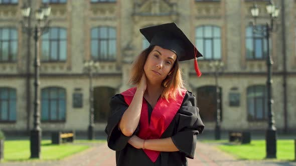 Thumbnail for Portrait of Confident Girl in Black Mantle and Cap Standing in Front of University Building