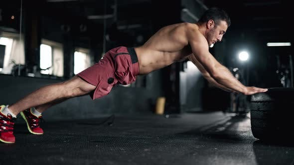 A Handsome Young Muscular Sportsman is Doing Exercise