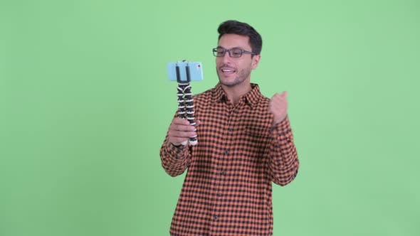 Happy Young Hispanic Hipster Man Vlogging and Showing Phone