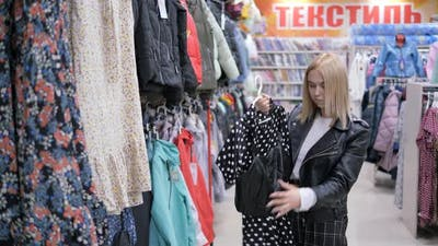 Woman Examines the Price Tag of a Dress