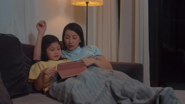Young Asian family and daughter happy using tablet at home.