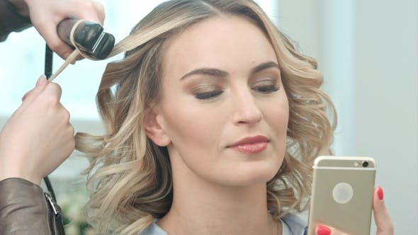 Cover Image for Young Pretty Woman Use Smartphone in Beauty Salon While