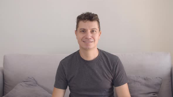 Thumbnail for Happy Handsome Man Wearing Casual T-shirt, Sitting on Couch