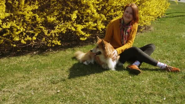 Thumbnail for Girl Playing With The Corgi On A Lawn