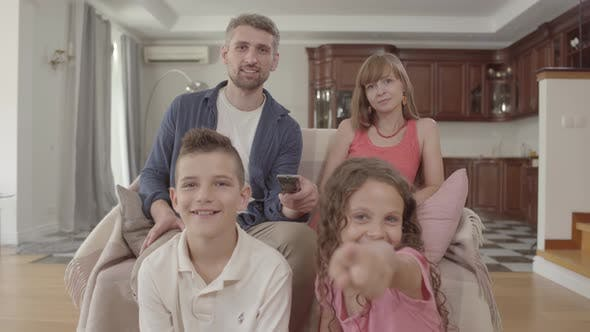 Thumbnail for Joyful Young Family Watching TV While Sitting at Home Together. The Father Holds the Remote and