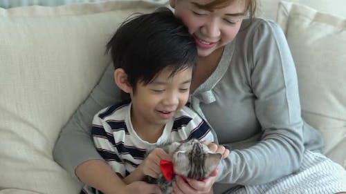 Asiatische Familie spielt mit Kätzchen auf dem Sofa zu Hause Zeitlupe