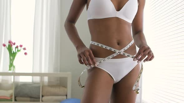 Thumbnail for Healthy Black woman measuring waist on diet