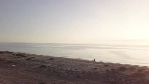 Man running on the beach. Orbital shot with drone