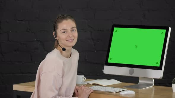 Thumbnail for Smiling Woman Looking Into Camera with Headset and Computer Monitor. Green Screen Mock-up Display.