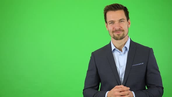 Thumbnail for A Young Handsome Businessman Presents Something To the Camera with a Smile - Green Screen Studio
