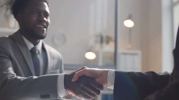 Close-Up of Black Businessman Shaking Hands and Speaking with Colleague