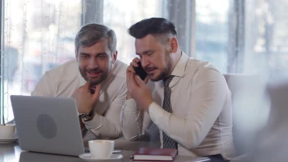 Cover Image for Two Cheerful Businessmen Using Laptop in Café
