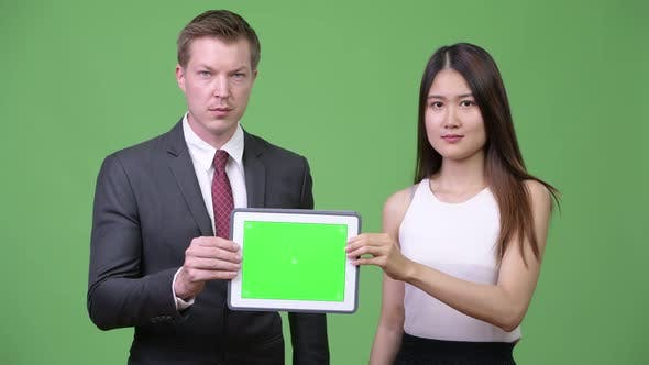Thumbnail for Multi-ethnic Business Couple Showing Digital Tablet Together
