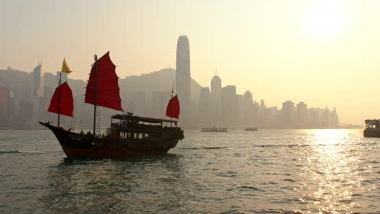 Cover Image for Sunset skyline of Hong Kong with traditional cruise sailboat at Victoria harbor