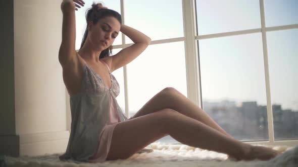 Thumbnail for Beautiful Girl in Nightie Sitting Near Window From Floor-to-ceiling. Young Woman in Pajamas