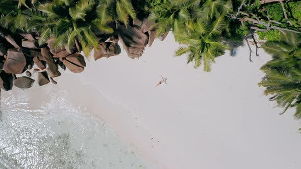 Thumbnail for Aerial Move Up Footage From Girl Laying on a Sandy Beach Surrounded By Crystal Clear Turquoise