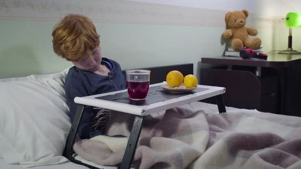 Thumbnail for Sad Caucasian Redhead Boy Lying in Bed and Drinking Hot Fruit Tea. Portrait of Sick Child Staying