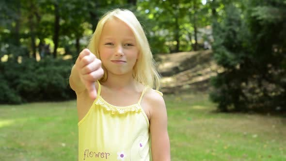 Thumbnail for Little Girl Shows Thumb Down and Shakes with Head - Disagree - Located in the Park
