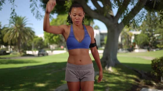 Thumbnail for Mixed race millennial woman athlete warming up for run outdoors
