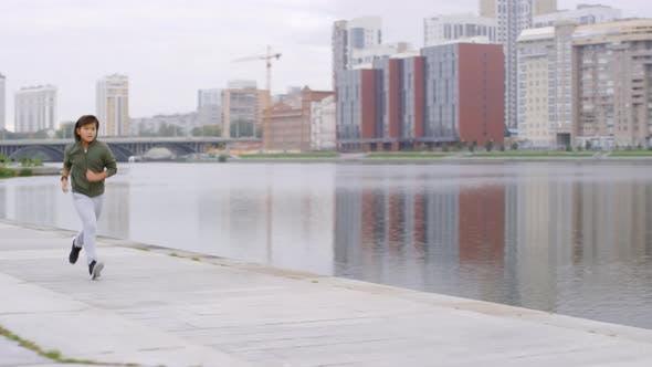 Thumbnail for Young Asian Boy Running along Riverside Sidewalk in City