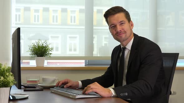 Thumbnail for An office worker in a suit sits at a desk in front of a computer and does gesture of invitation