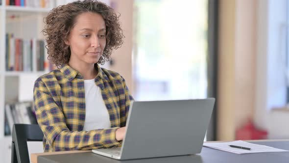 Attractive Young Mixed Race Woman with Laptop Pointing at Camera