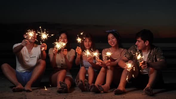 Young holding fireworks on beach