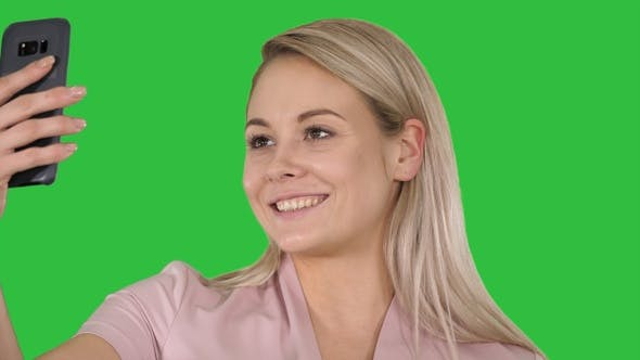 Thumbnail for Smiling young blonde girl taking a selfie on a Green Screen