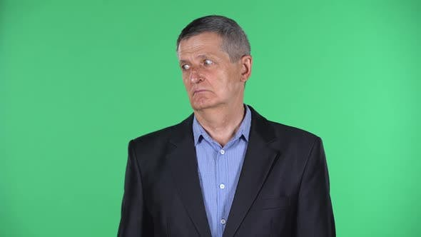 Portrait of Aged Man Looking Straight and Listens Carefully To Someone Isolated Over Green