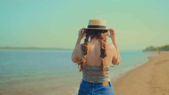 Young Woman Walks Along the Seashore and Enjoys