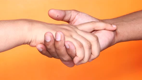 Thumbnail for Close Up of Couple Holding Hands Against Orange Background.