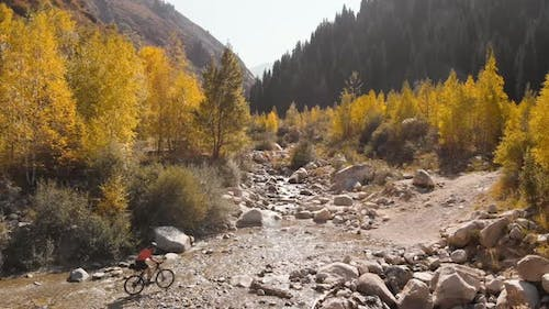 Man Is Crossing the River By Bicycle in the Mountains Shot By Drone