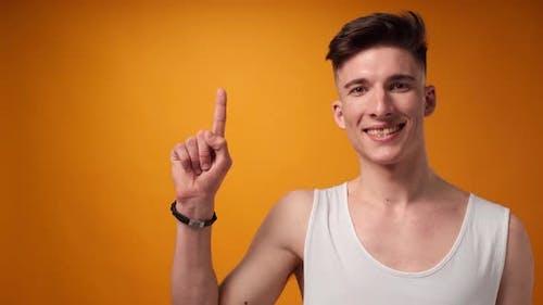 Junger Mann zeigt auf Kopierraum für Werbung gelbem Hintergrund