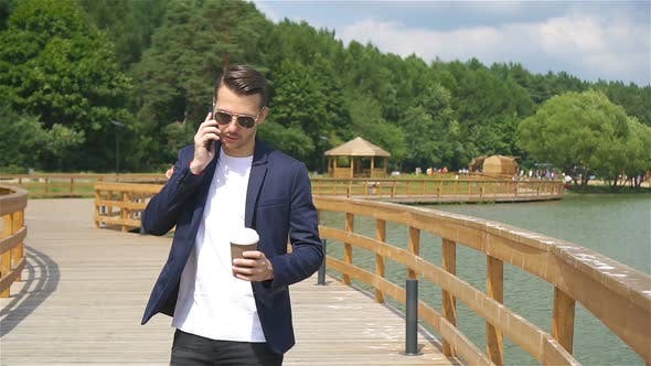 Happy Young Urban Man Drinking Coffee in European City Outdoors