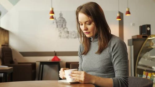 Women is Drinking a Cup of Coffee Sitting in Cafe