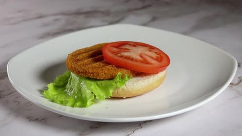 Process of Assembling a Fish Burger on a White Plate